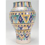 A late 19th / early 20th Century Moroccan pottery vase of waisted form having hand painted