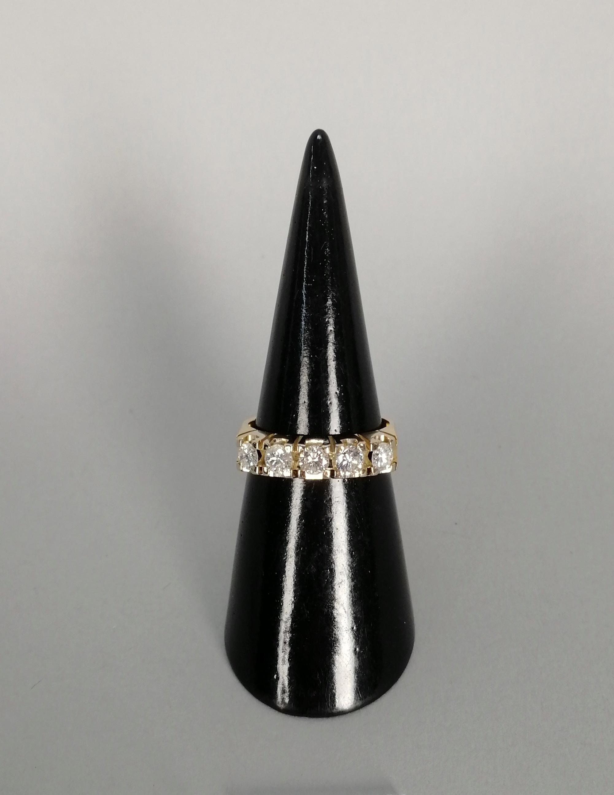 Lot 10 - Anello in oro bianco e giallo 18 kt. con cinque diamanti, gr. 7 ca. complessivi. Misura 15