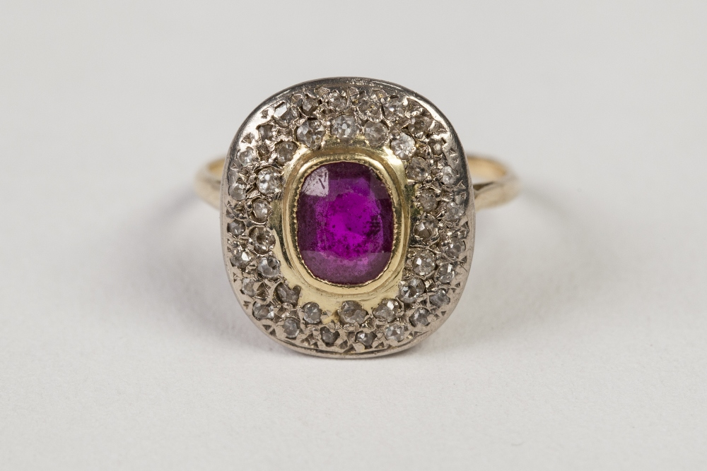 Lot 47 - ANTIQUE GOLD COLOURED METAL RING, collet set with a centre rounded oblong ruby and pave surround