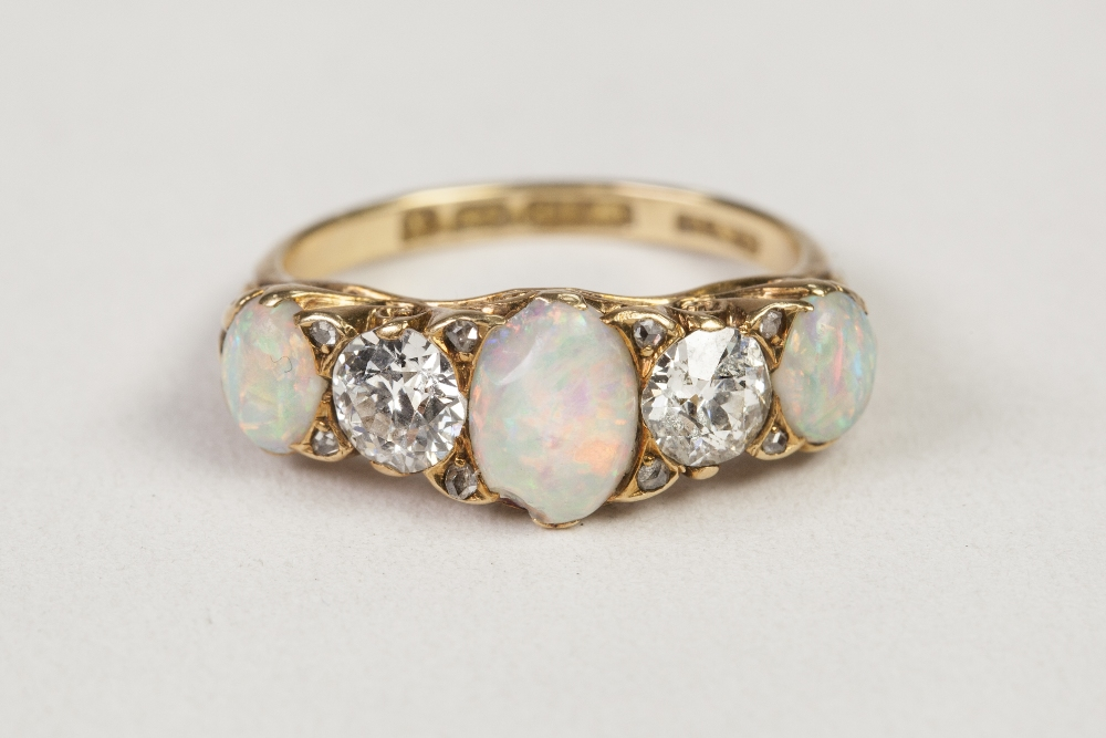 Lot 38 - VICTORIAN 18ct GOLD, DIAMOND AND OPAL RING, with a carved setting of three oval opals, two round old