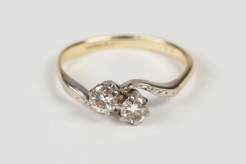 Lot 43 - 18ct GOLD AND PLATINUM CROSS OVER RING, set with two round brilliant cut diamonds, each approx 1/