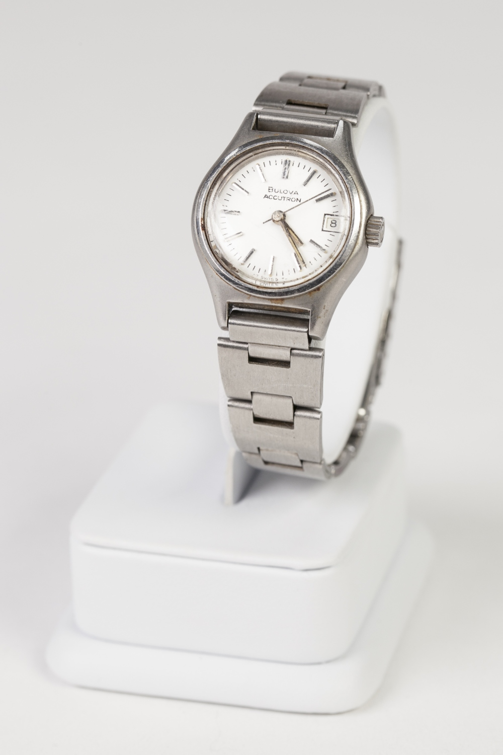 """Lot 24 - BULOVA """"ACCUTRON"""" MID SIZE STAINLESS STEEL CASED WRIST WATCH white enamel dial with date aperture,"""
