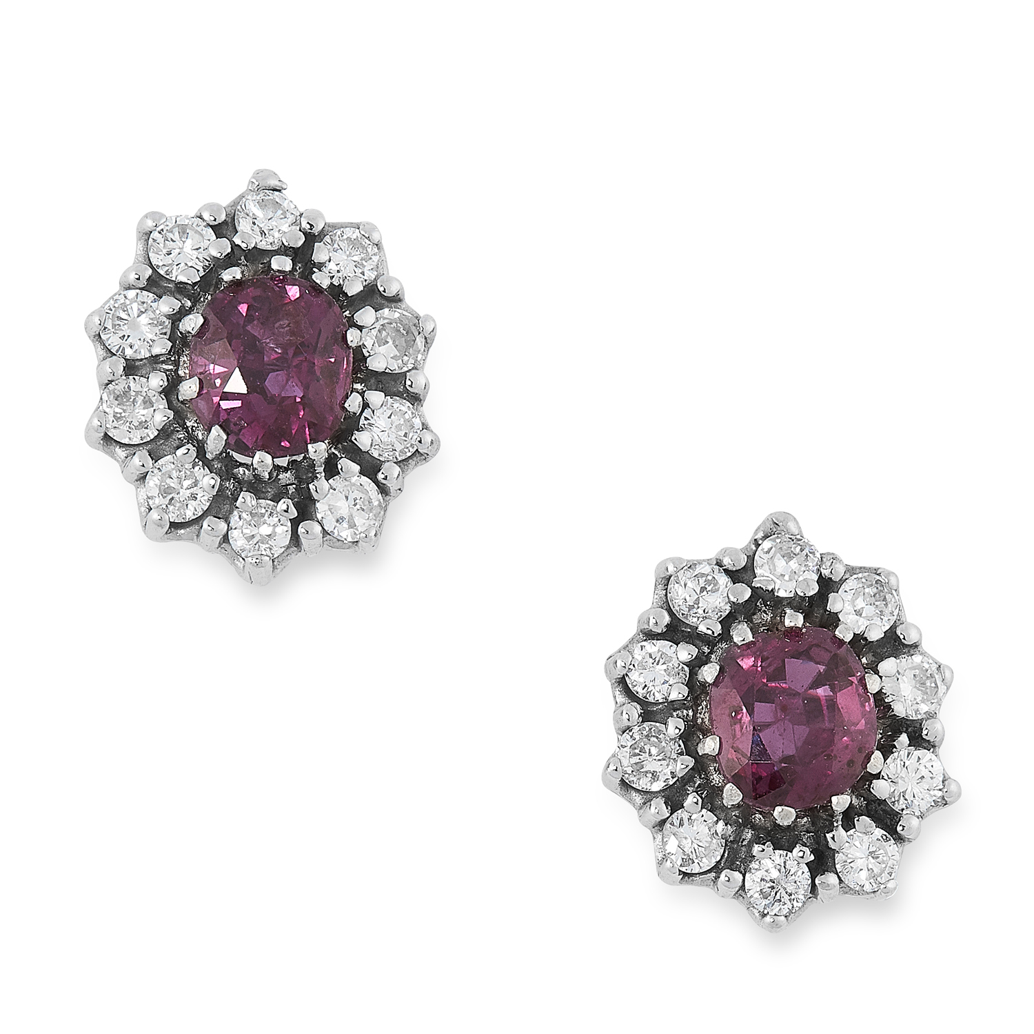 A PAIR OF RUBY AND DIAMOND CLUSTER STUD EARRINGS each set with an oval cut ruby encircled by round