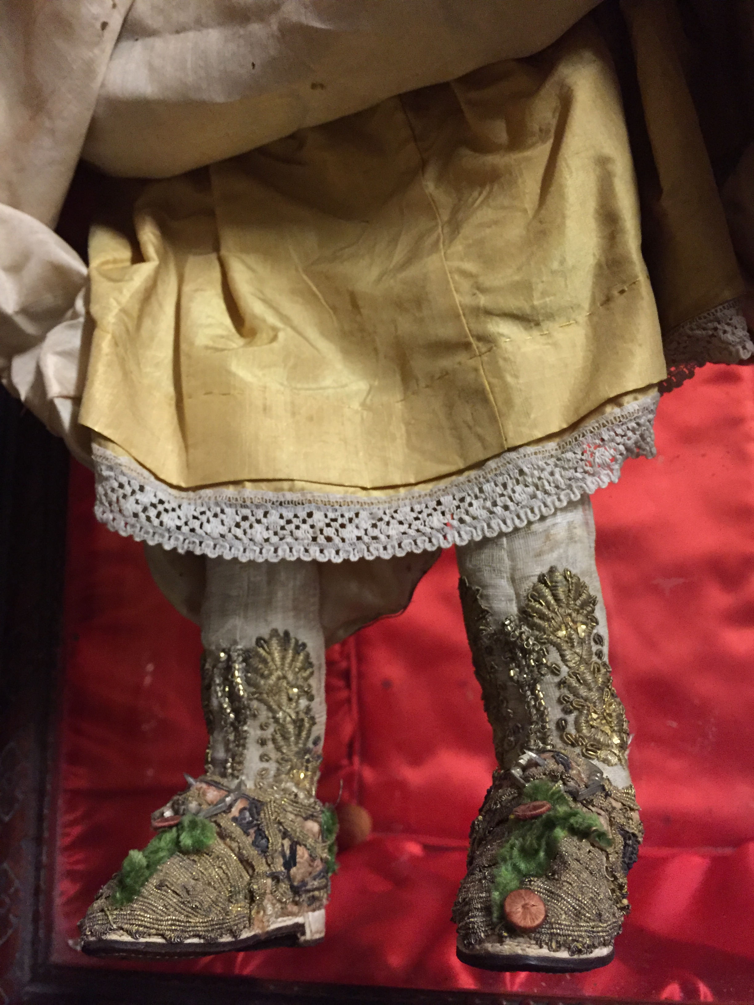 Lot 349 - A RARE AND UNUSUAL 18TH CENTURY POURED WAX DOLL Relief moulded hair and dark glass eyes, wearing a