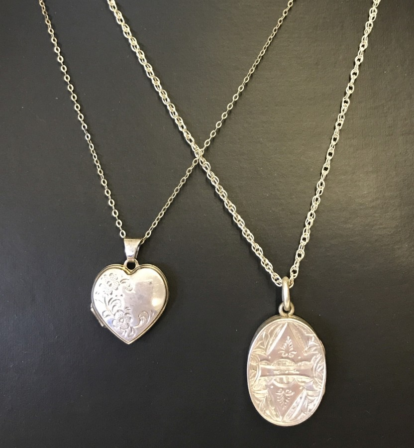 Lot 1008 - 2 white metal lockets on chains.