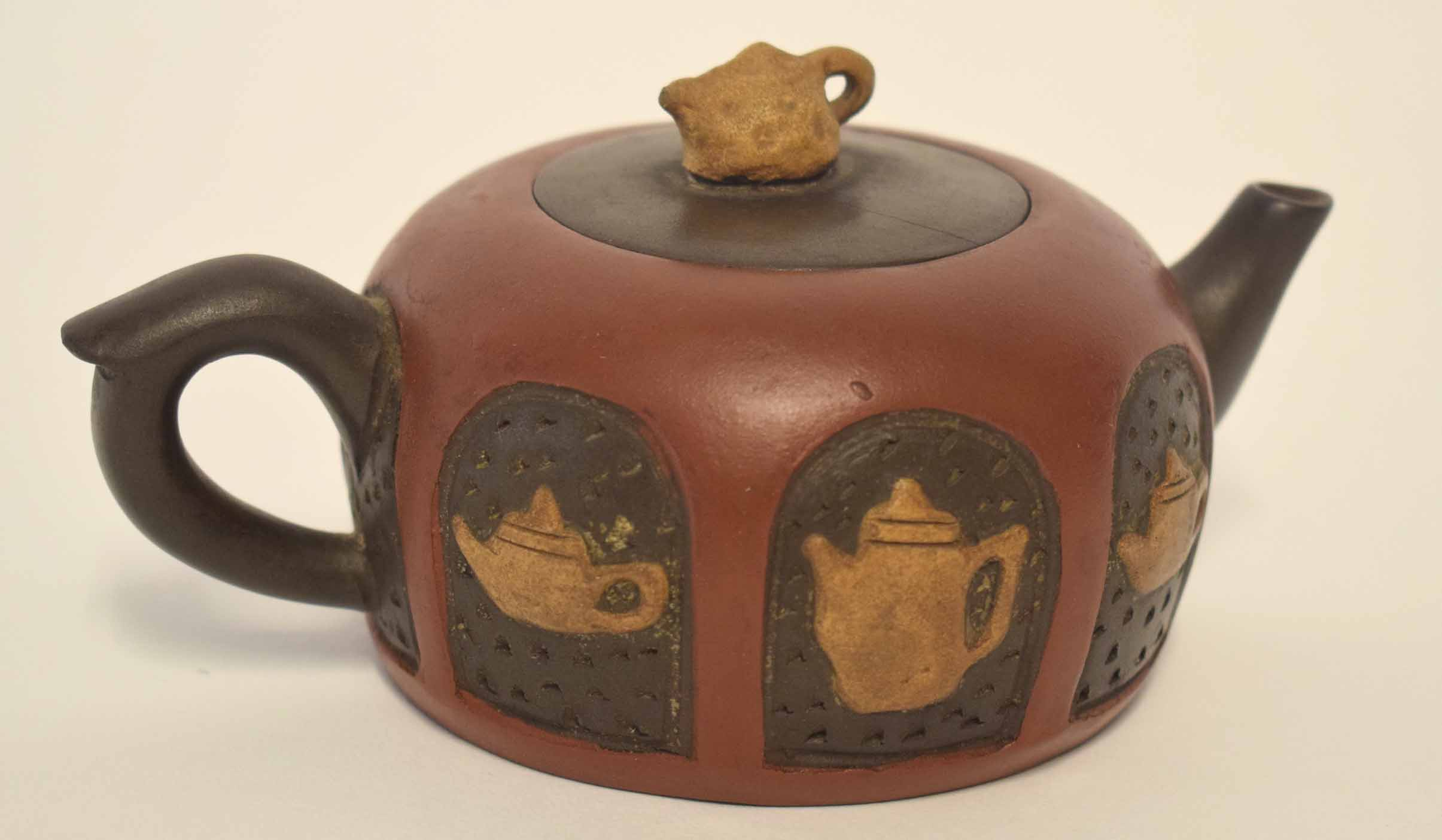 Lot 15 - Chinese red ware teapot and cover, the body decorated with tea and coffee pot motifs, the cover with