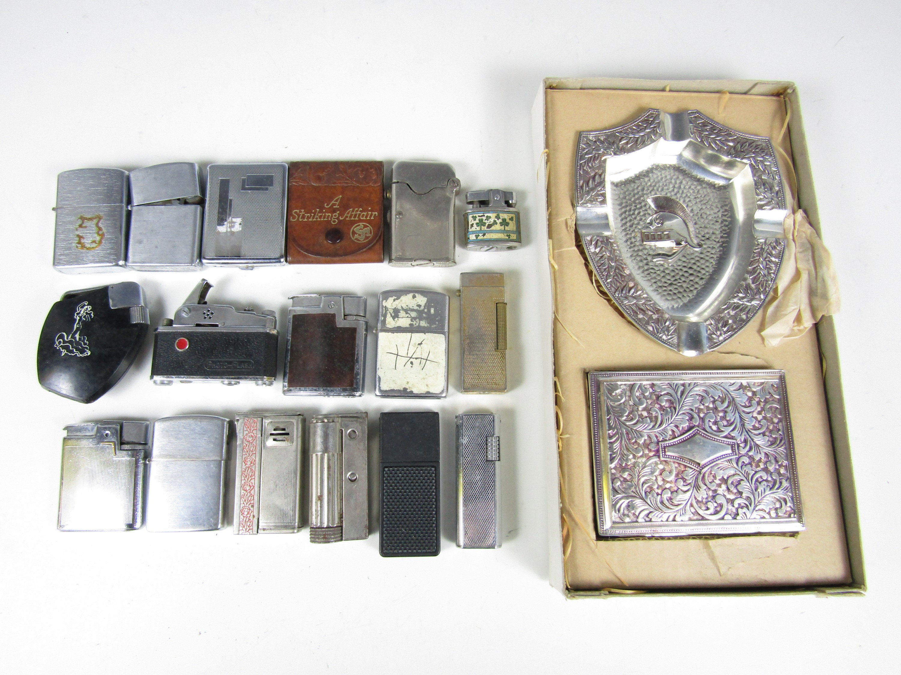 Lot 25 - A quantity of vintage cigarette lighters and related material including a KKW camera lighter