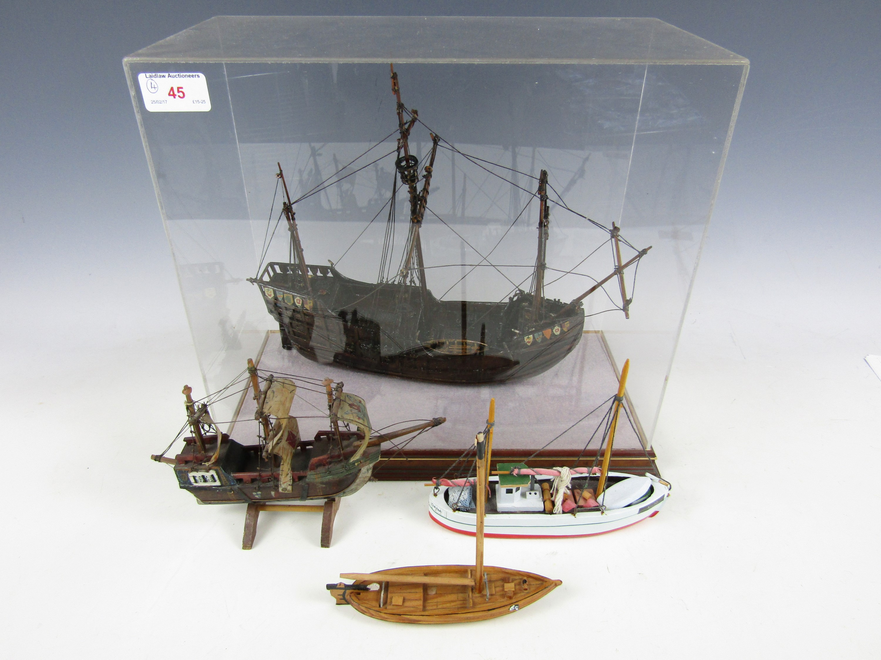 Lot 45 - A cased model galleon together with three small wooden ships