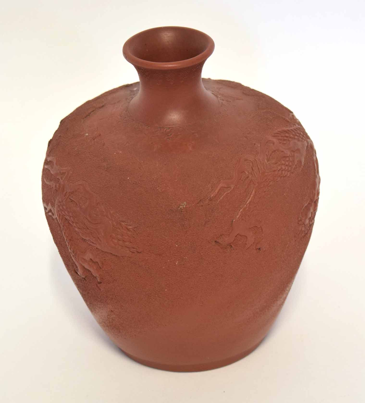 Lot 17 - Chinese red ware vase, the body carved in relief with a sinuous dragon, 19cm high