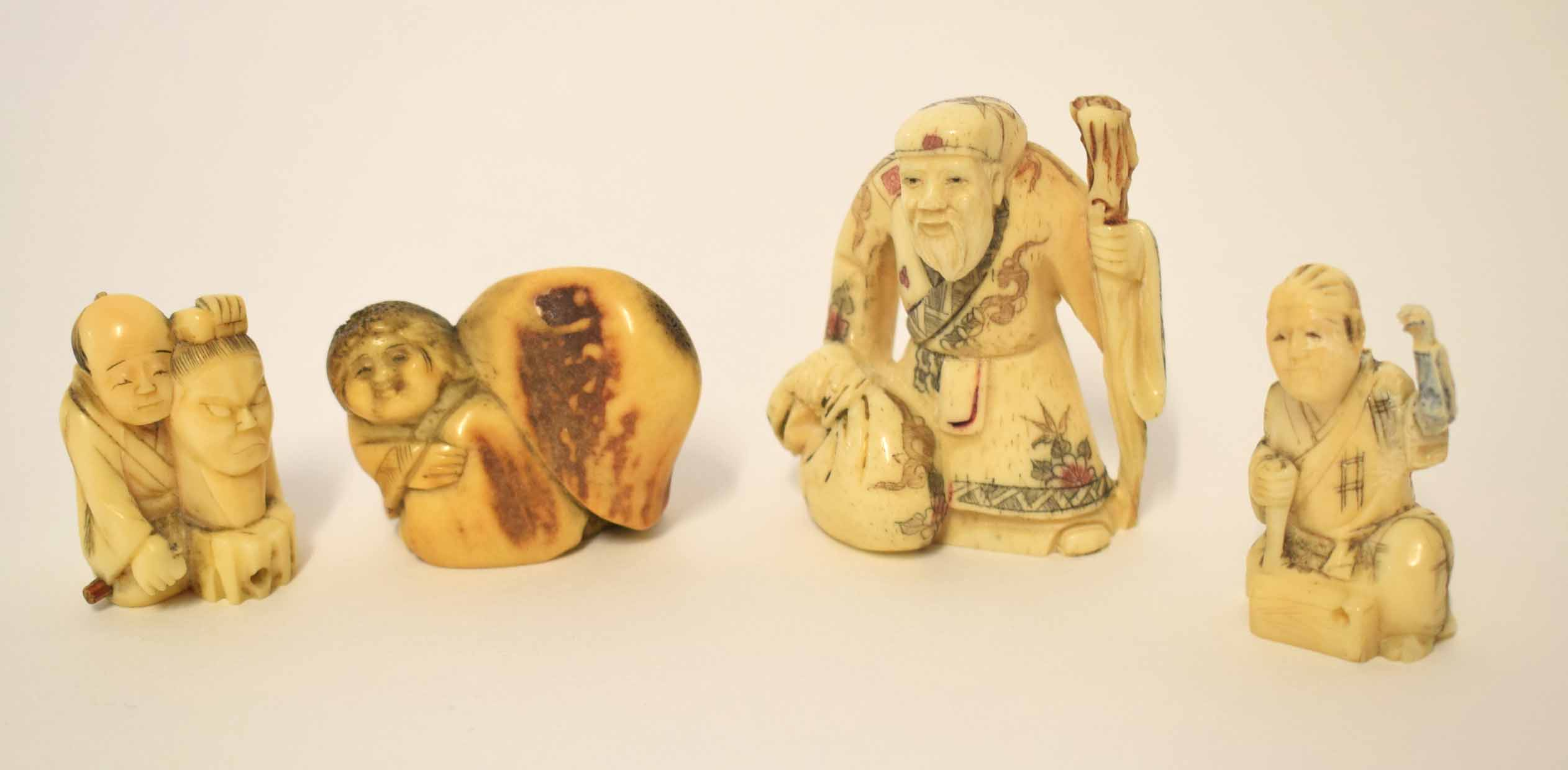 Lot 5 - Group of Oriental carvings and netsuke comprising a carving of an immortal with staff plus three