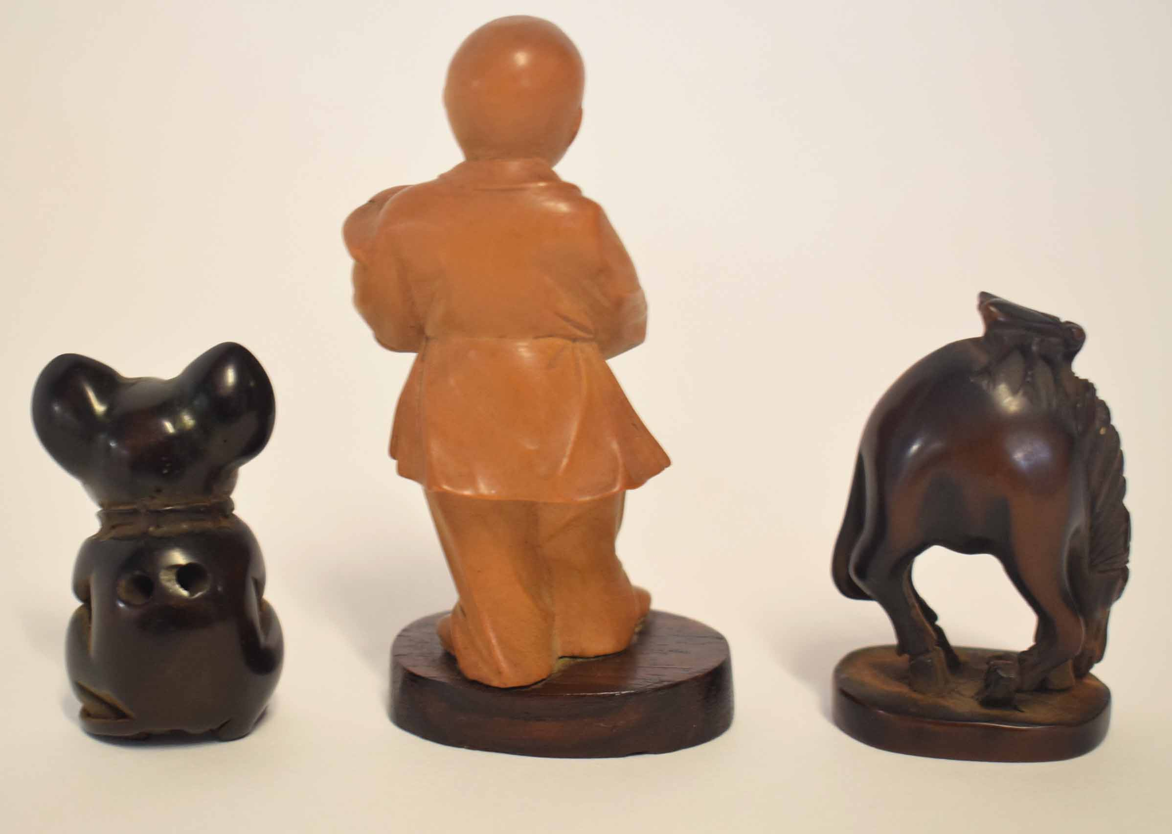 Lot 4 - Carved Oriental figure of a boy together with two further wooden carvings, model of a gazelle and