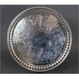 A Victorian silver circular tray with engraved floral decoration, the pierced border with