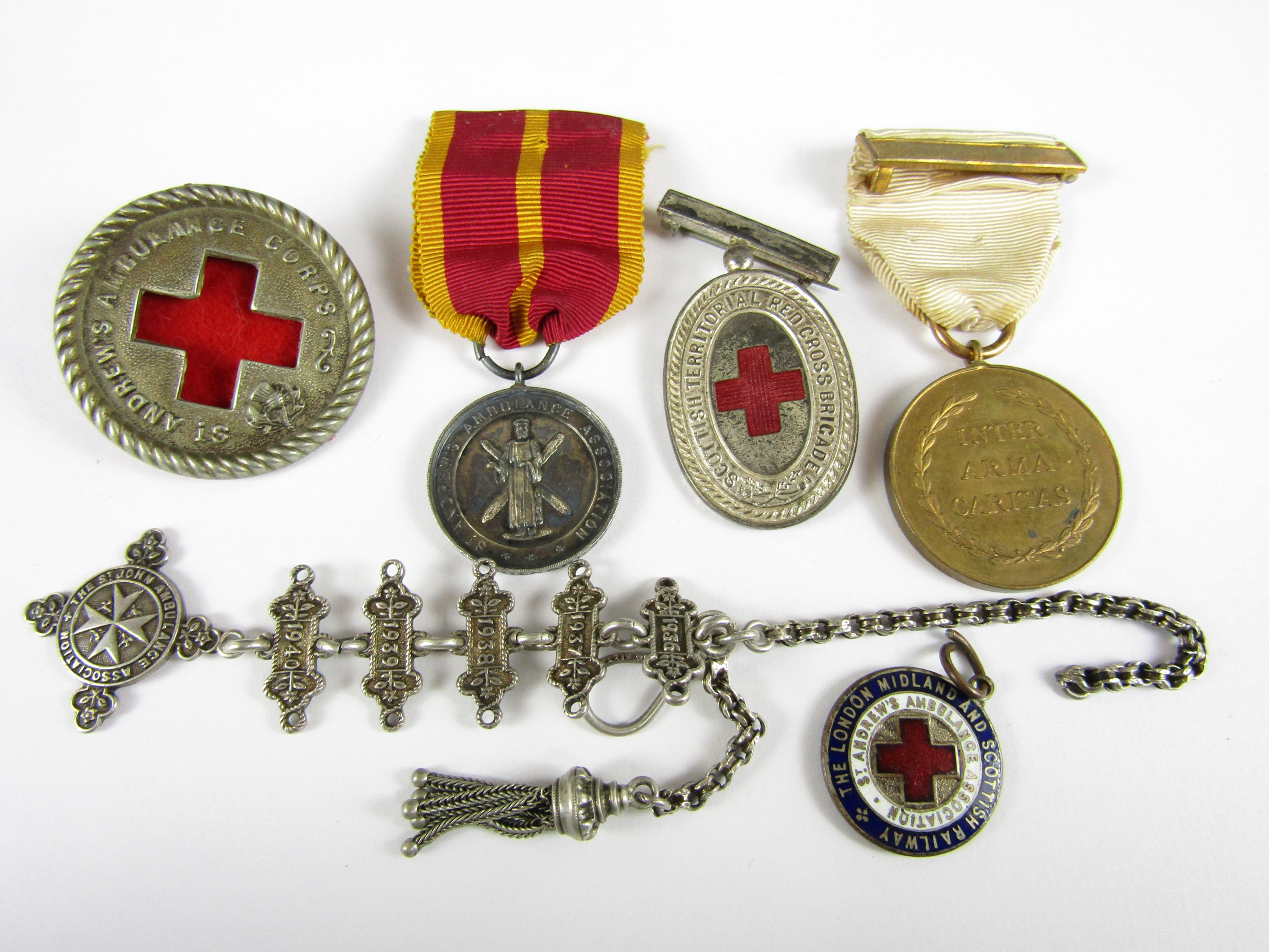 Lot 60 - A group of Red Cross and similar medals and insignia including a silver watch chain and a London