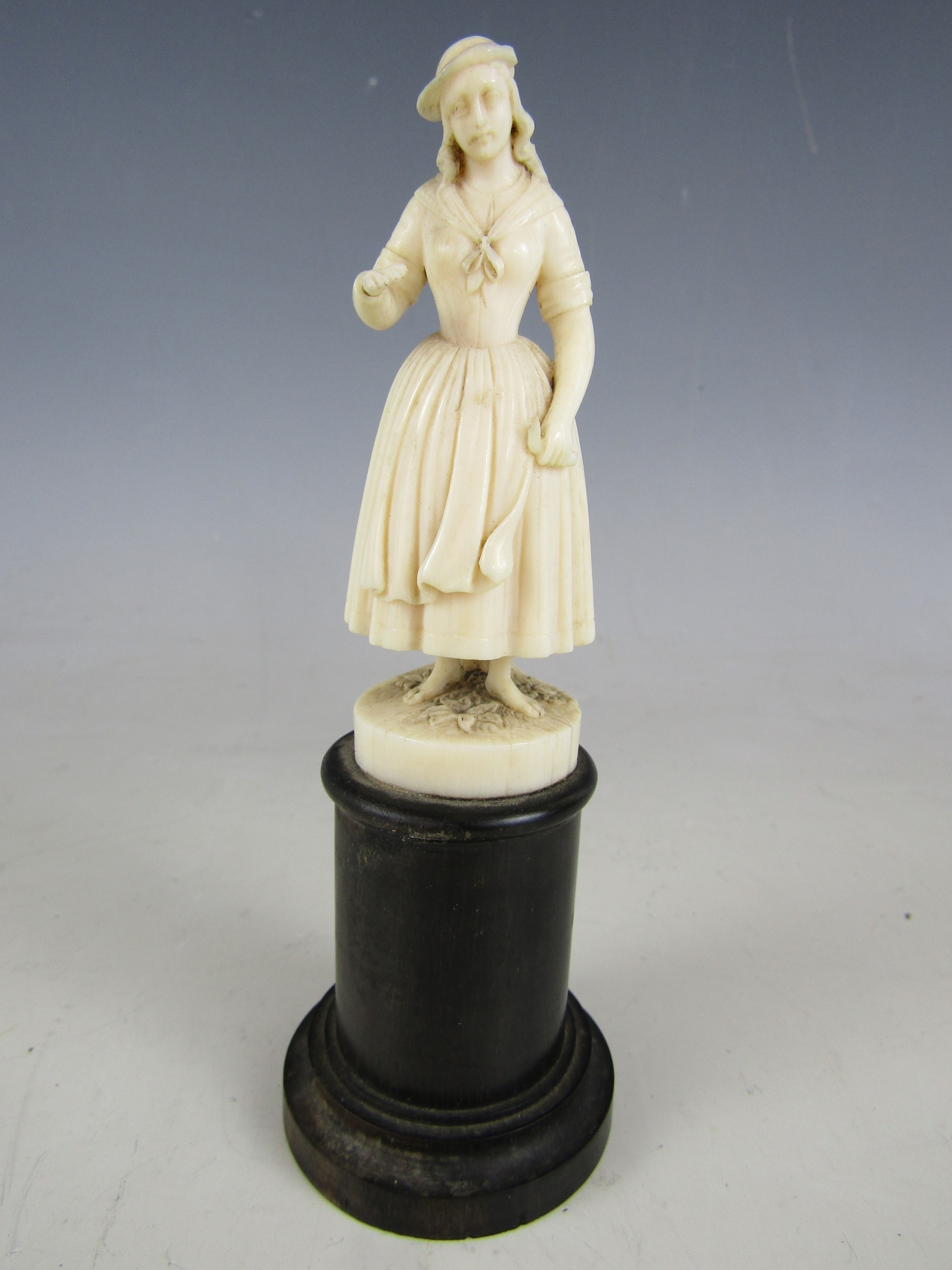 Lot 19 - A finely carved ivory statuette of an 18th Century peasant girl, on a turned ebony socle, 19th