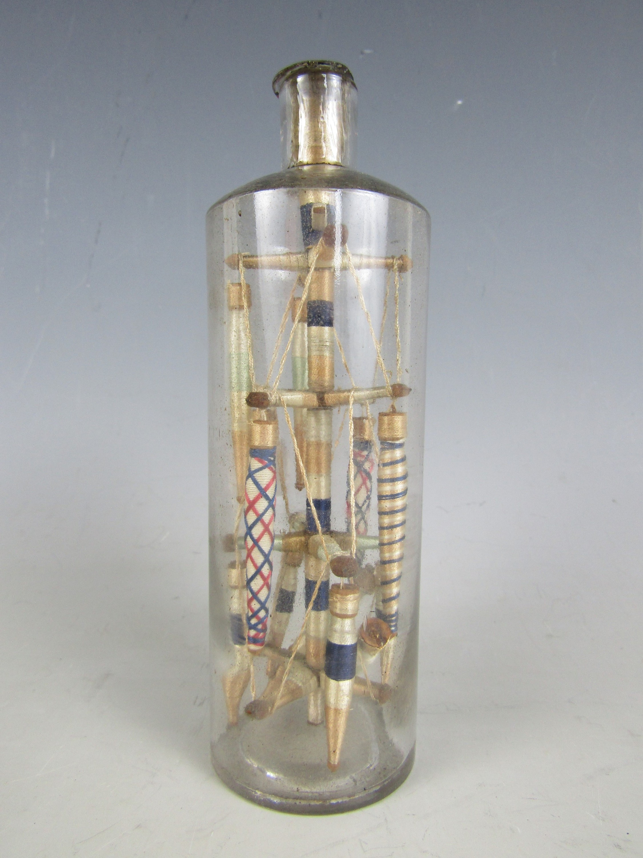 Lot 3 - A 19th Century folk art ornament of silk thread bobbins arranged in a glass bottle, 16 cm
