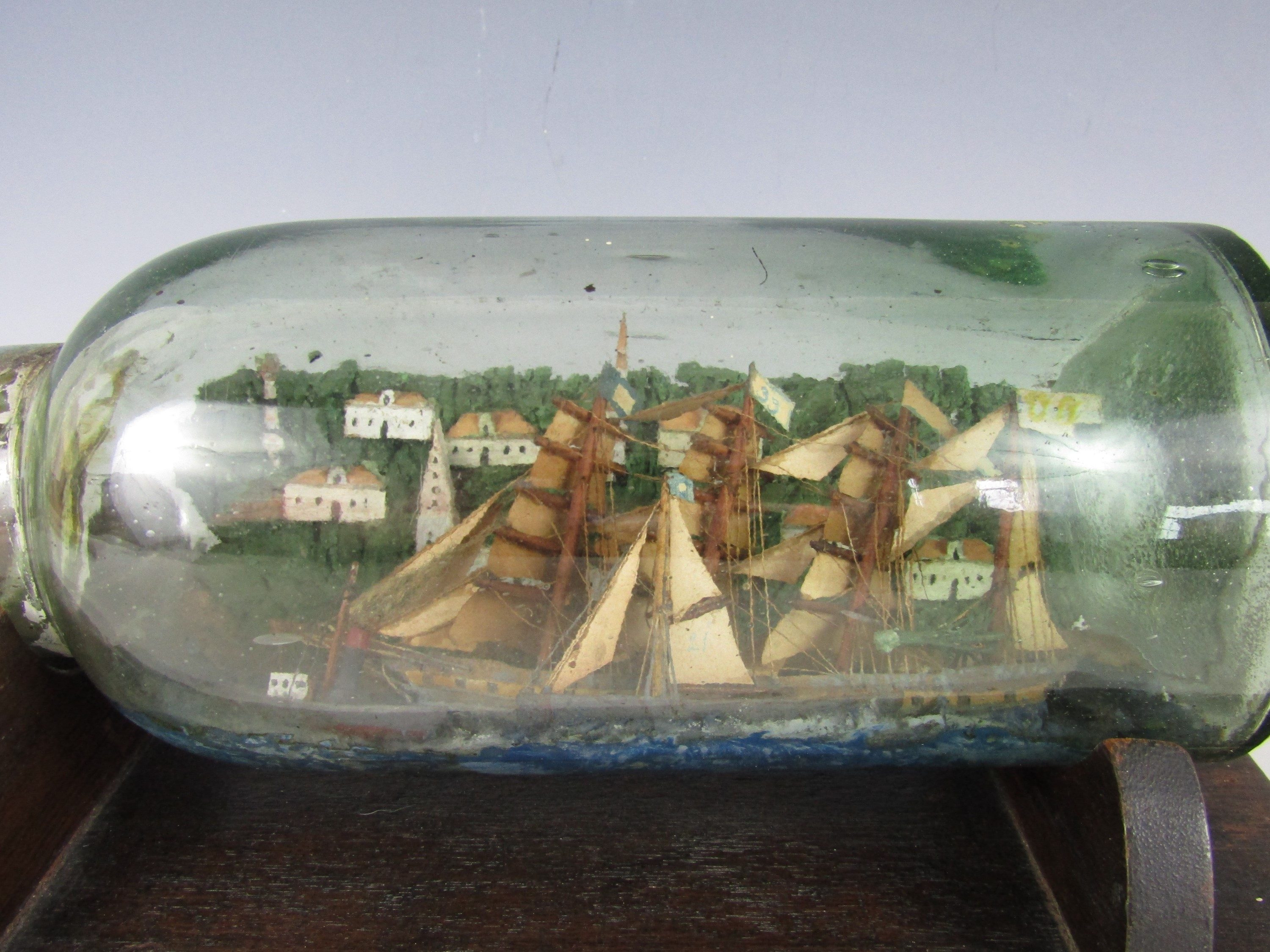 Lot 9 - A late 19th Century ship in a bottle, the four-masted sailing vessel accompanied in the water by a