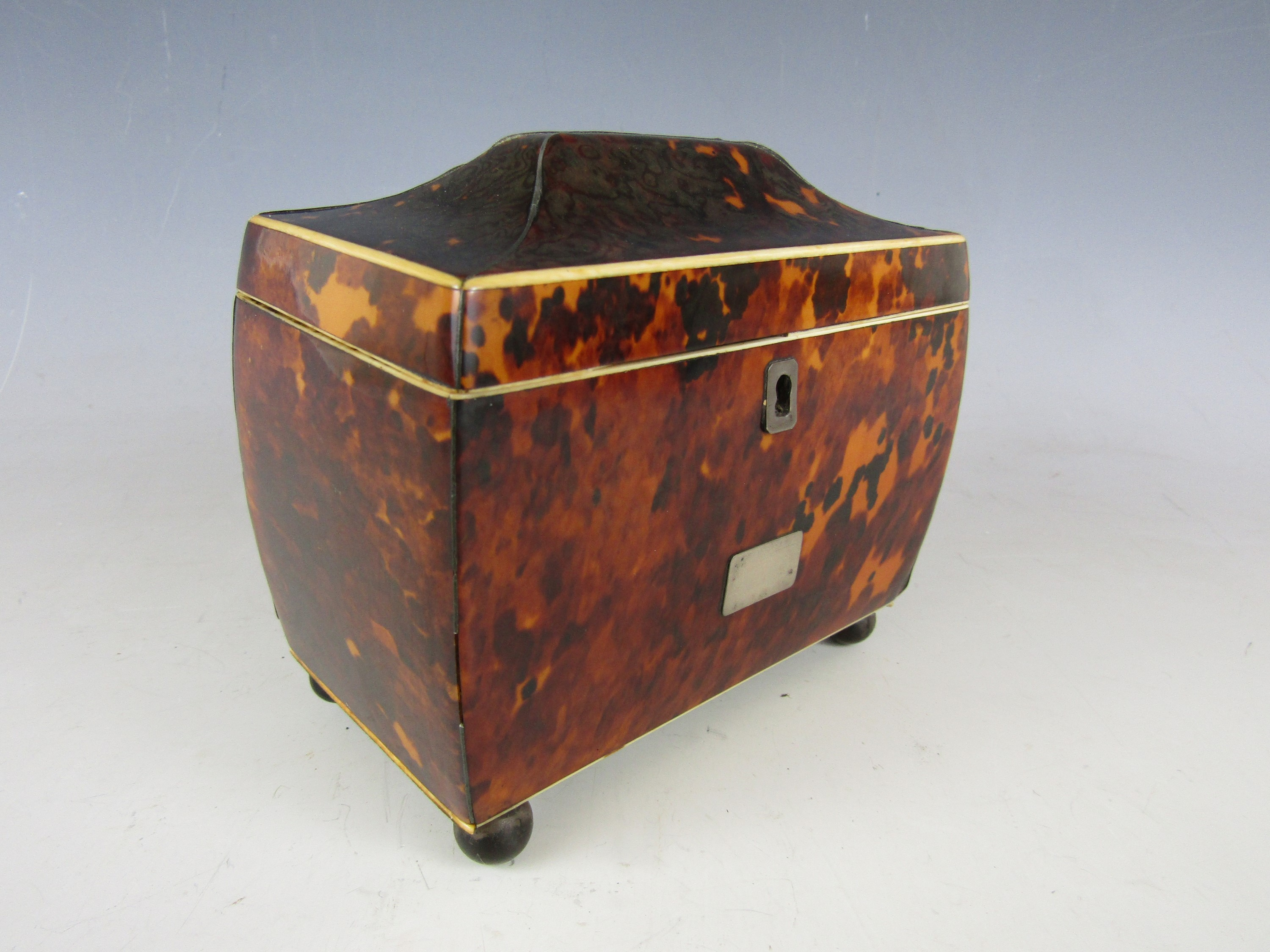 Lot 13 - A Regency tortoiseshell tea caddy, of sarcophagus form with ivory and silver string inlay, opening