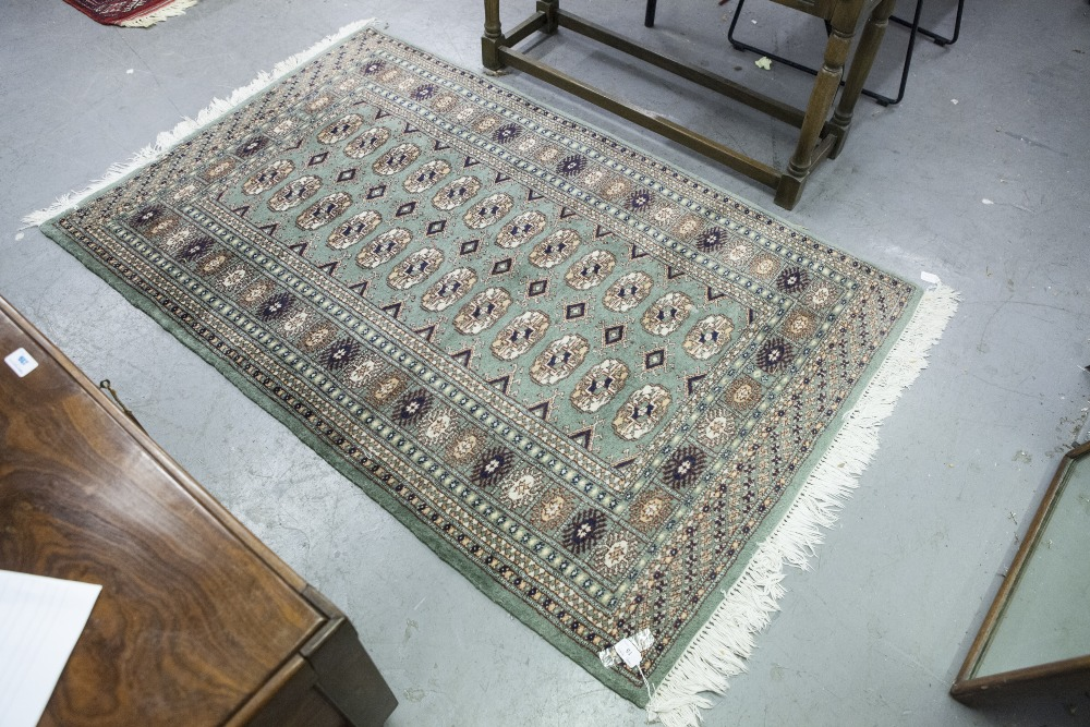 """Lot 15 - PAKISTAN BOKHARA RUG with two rows of guls on a green field, multiple border stripes, 5' x 3' 2"""" ("""