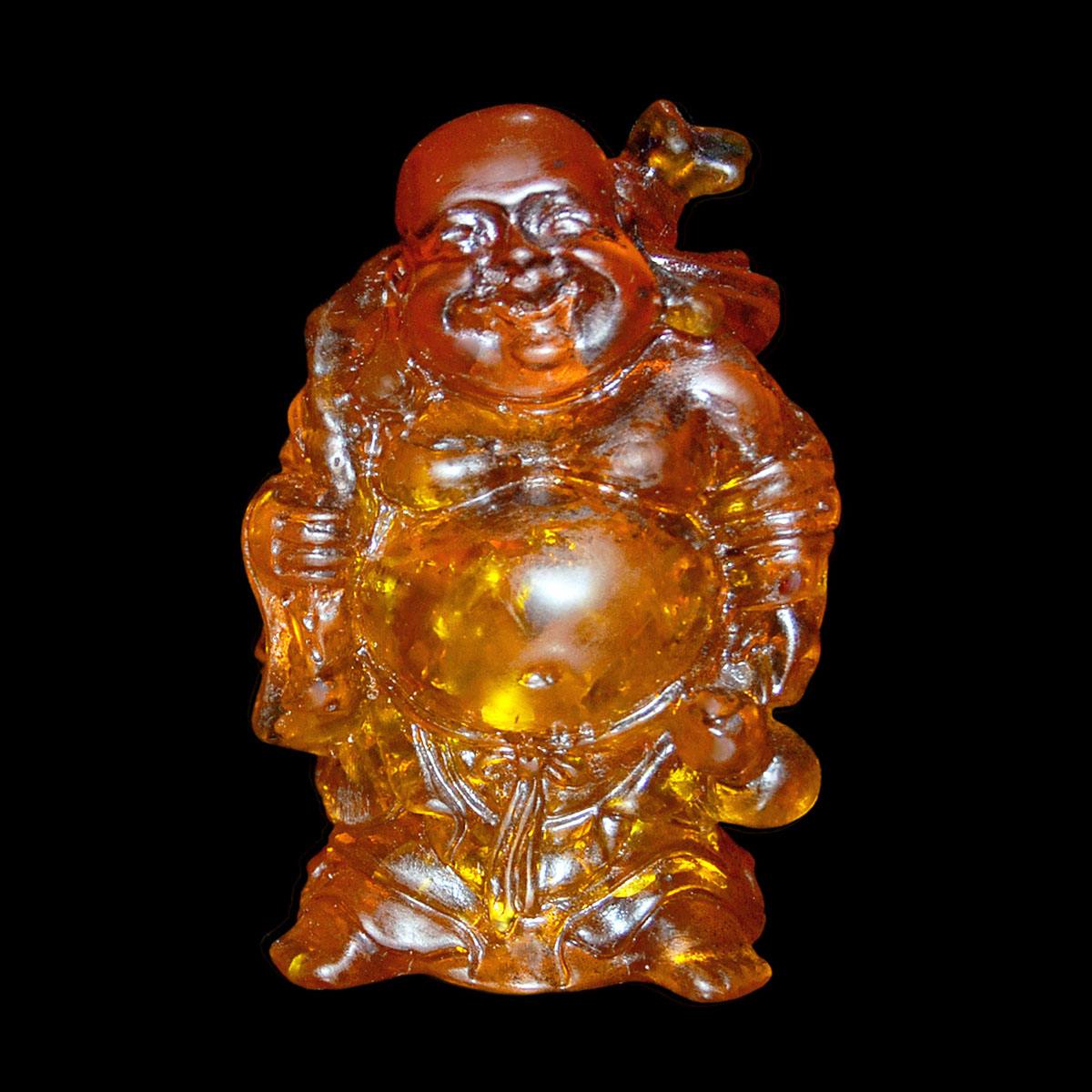 Lot 55 - 琥珀雕布袋和尚立像 An Amber Carving of Budai Carrying His Bag. Height: 3⅜ in (8.6 cm)  Weight: 154 g.
