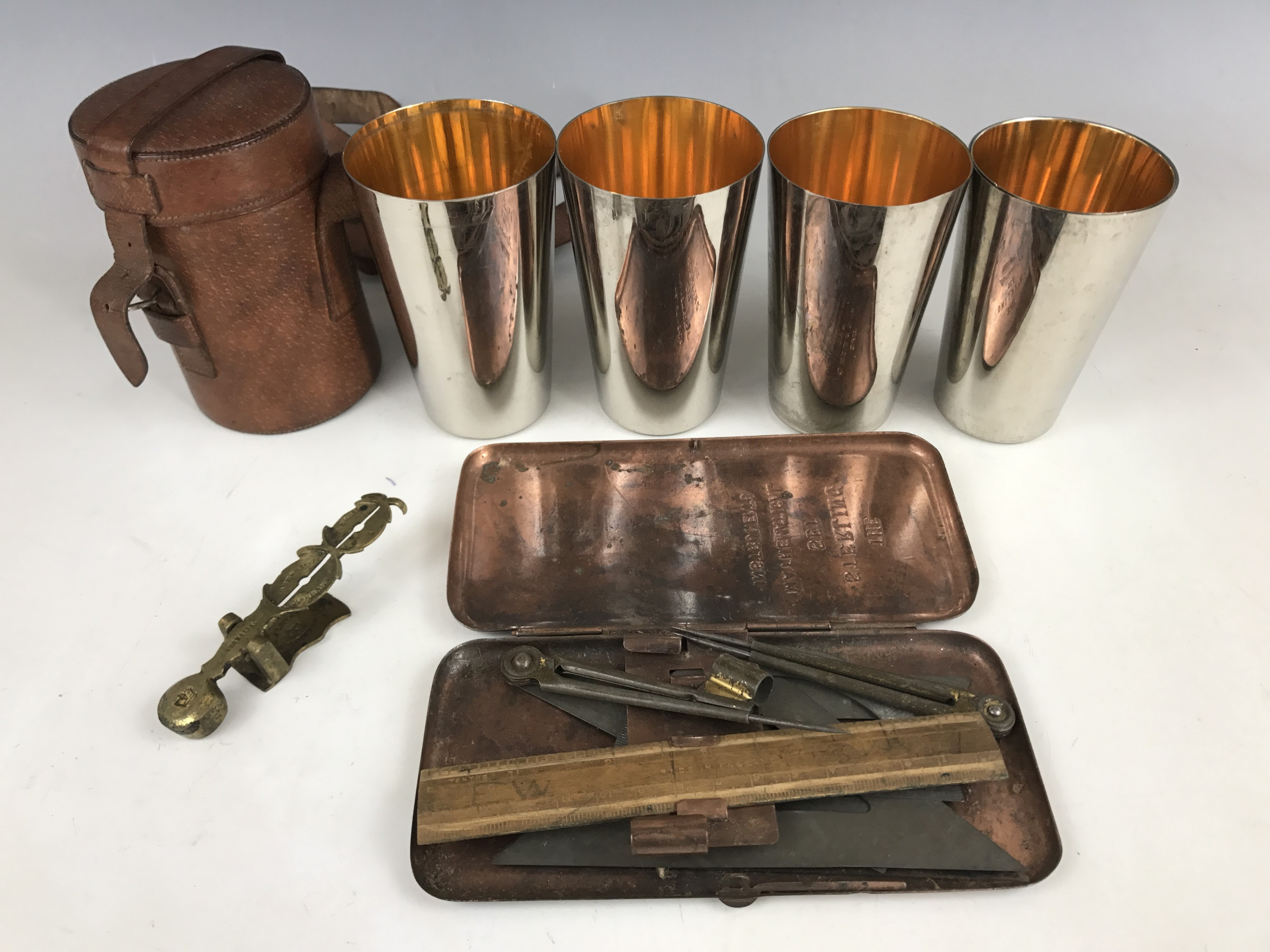 """Lot 39 - A vintage leather-cased set of four electroplate nesting / stacking beakers, together with a """""""