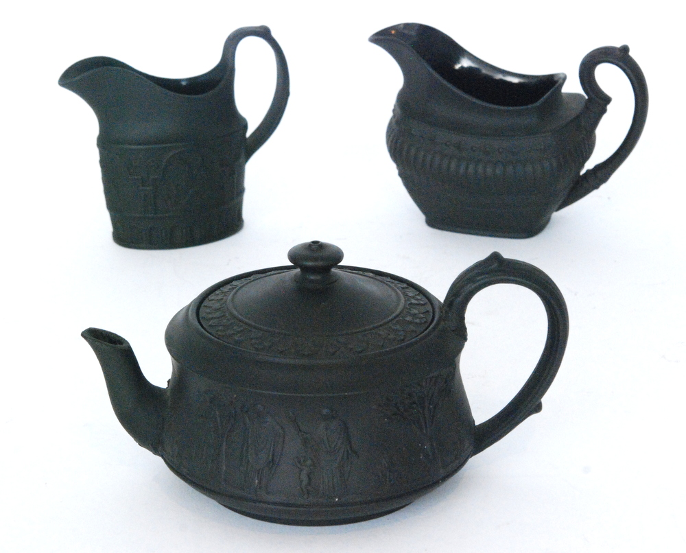 Lot 32 - Three pieces of black basalt comprising a 1930s Wedgwood teapot of compressed form decorated in low