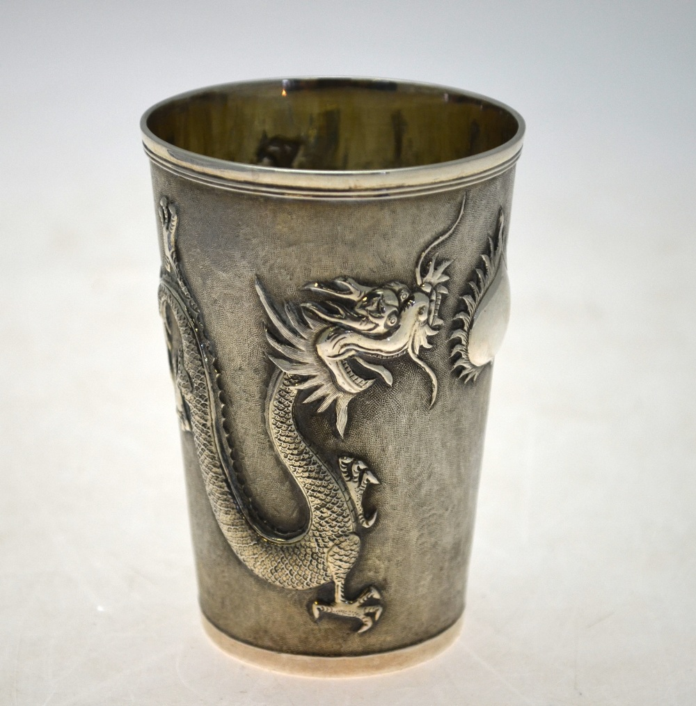 Lot 33 - A Chinese silver beaker of tapering form embossed and chased with dragons guarding a flaming peach,