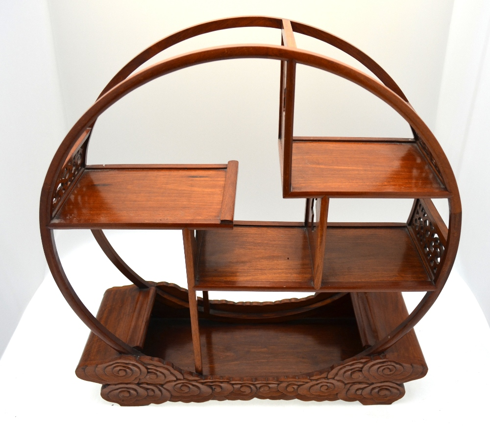 Lot 51 - A Japanese hardwood table stand, the open circular frame (sun or moon) raised on a cloud form base,
