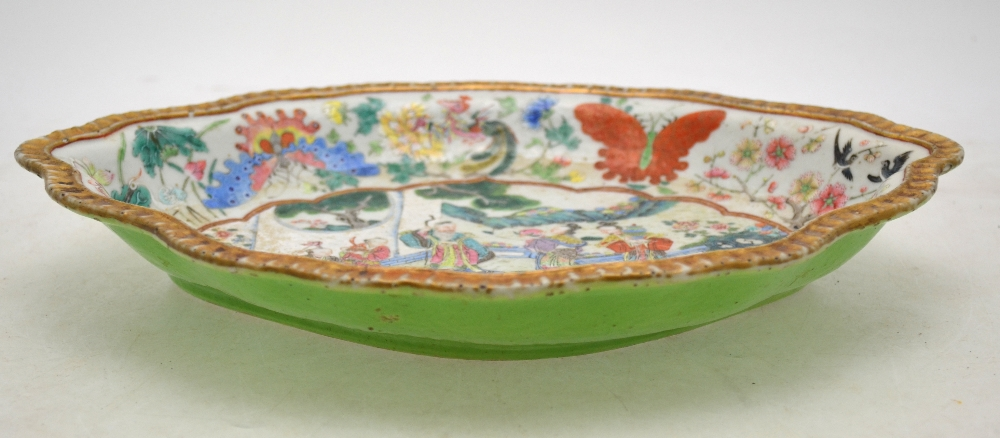 Lot 21 - A Chinese Canton famille rose shaped dish decorated with figures in a garden,