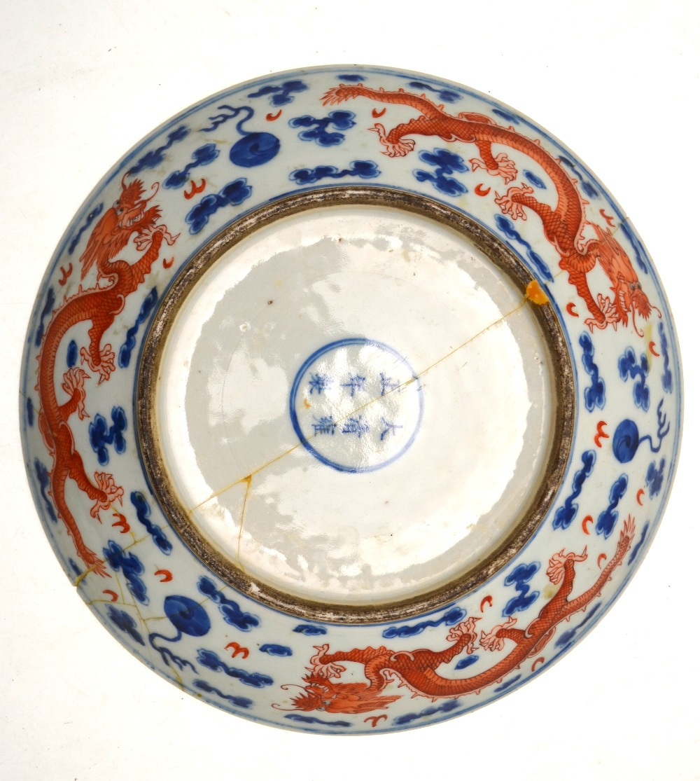Lot 31 - A Chinese circular dish decorated with a border of dragons chasing flaming pearls of wisdom,