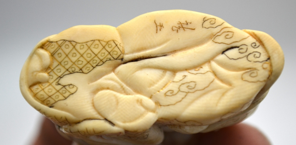 Lot 41 - A small Japanese okimono of a woman grooming a bald man, signed to base, 4.5 cm h.