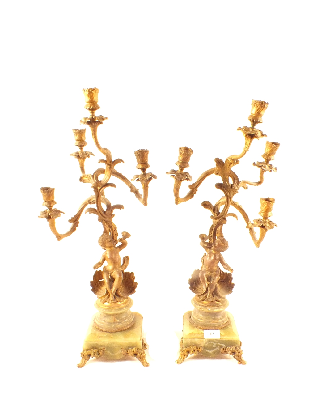 Lot 47 - A pair of green onyx and gilt metal four branch candelabra supported by horn blowing cherubs (as