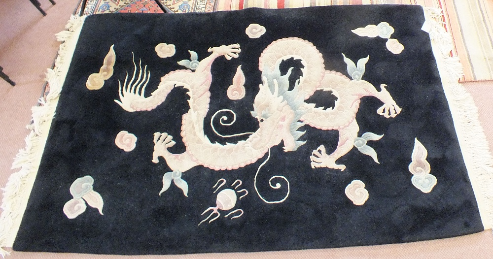 Lot 58 - A Chinese black ground rug with dragon and flaming pearl decoration,
