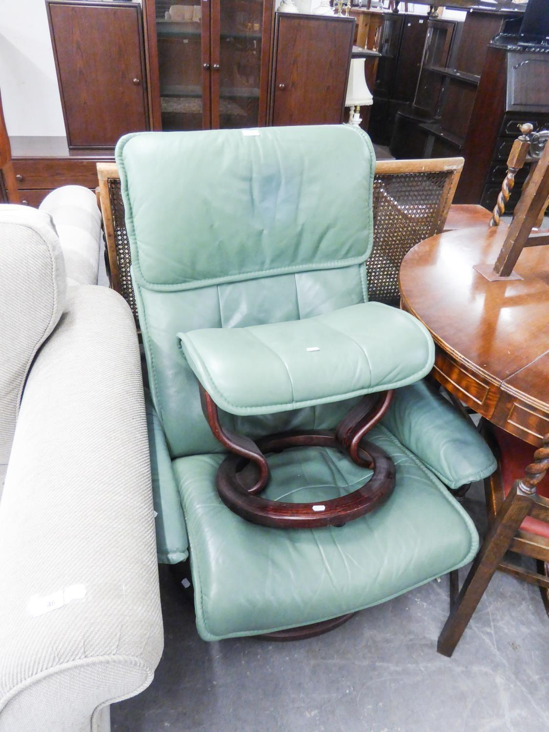 Lot 63 - GREEN HIDE EASY ARMCHAIR, revolving on a circular wooden base and the matching footstool, (2)