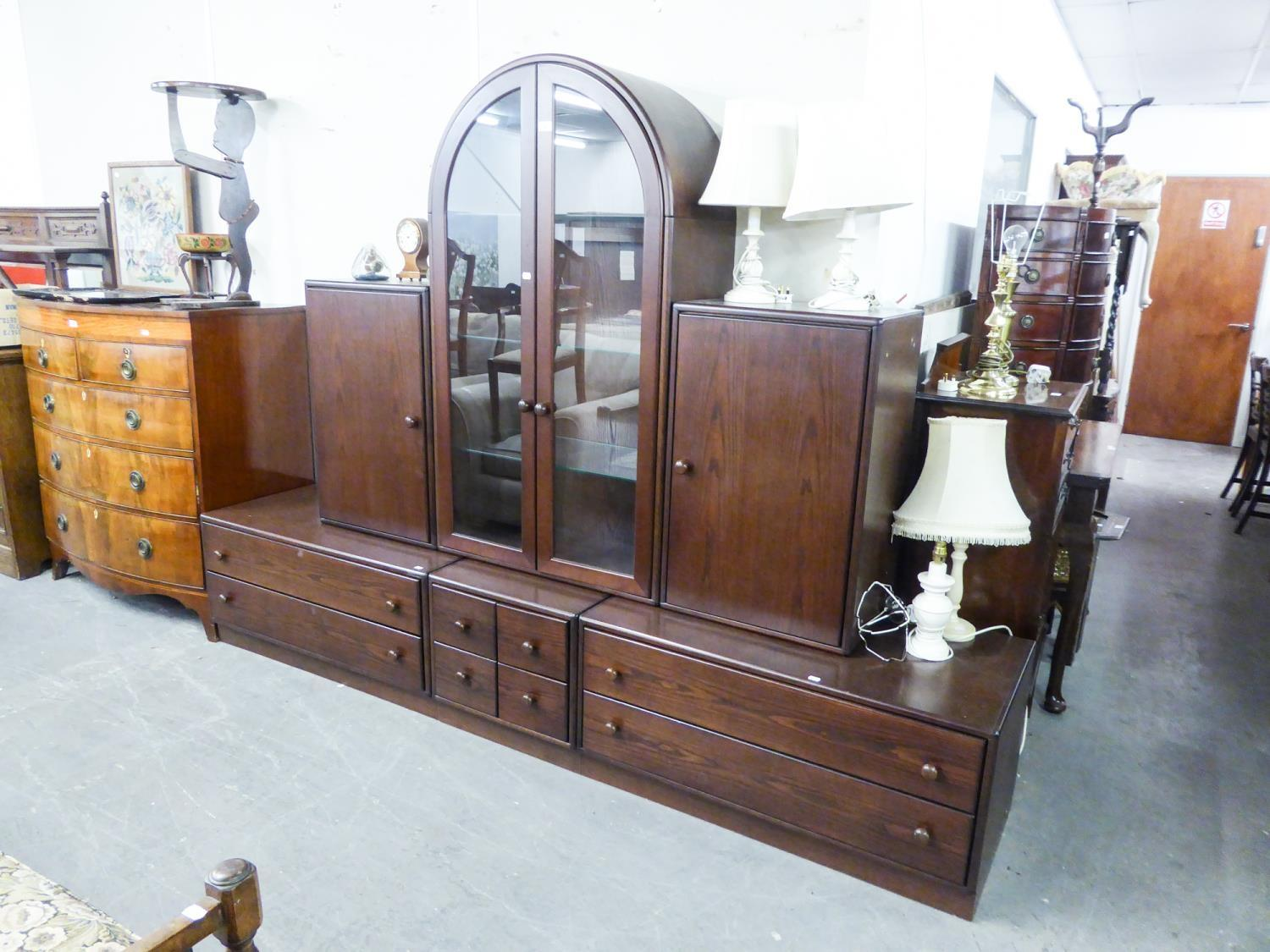 Lot 8 - A GOOD QUALITY 'HULSTA' DARK OAK LOUNGE UNIT, THE UPPER SECTION HAVING CENTRAL ARCH GLAZED DOORS,