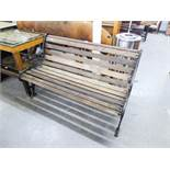 A GARDEN BENCH WITH DECORTIVE METAL SIDE WITH SLATS