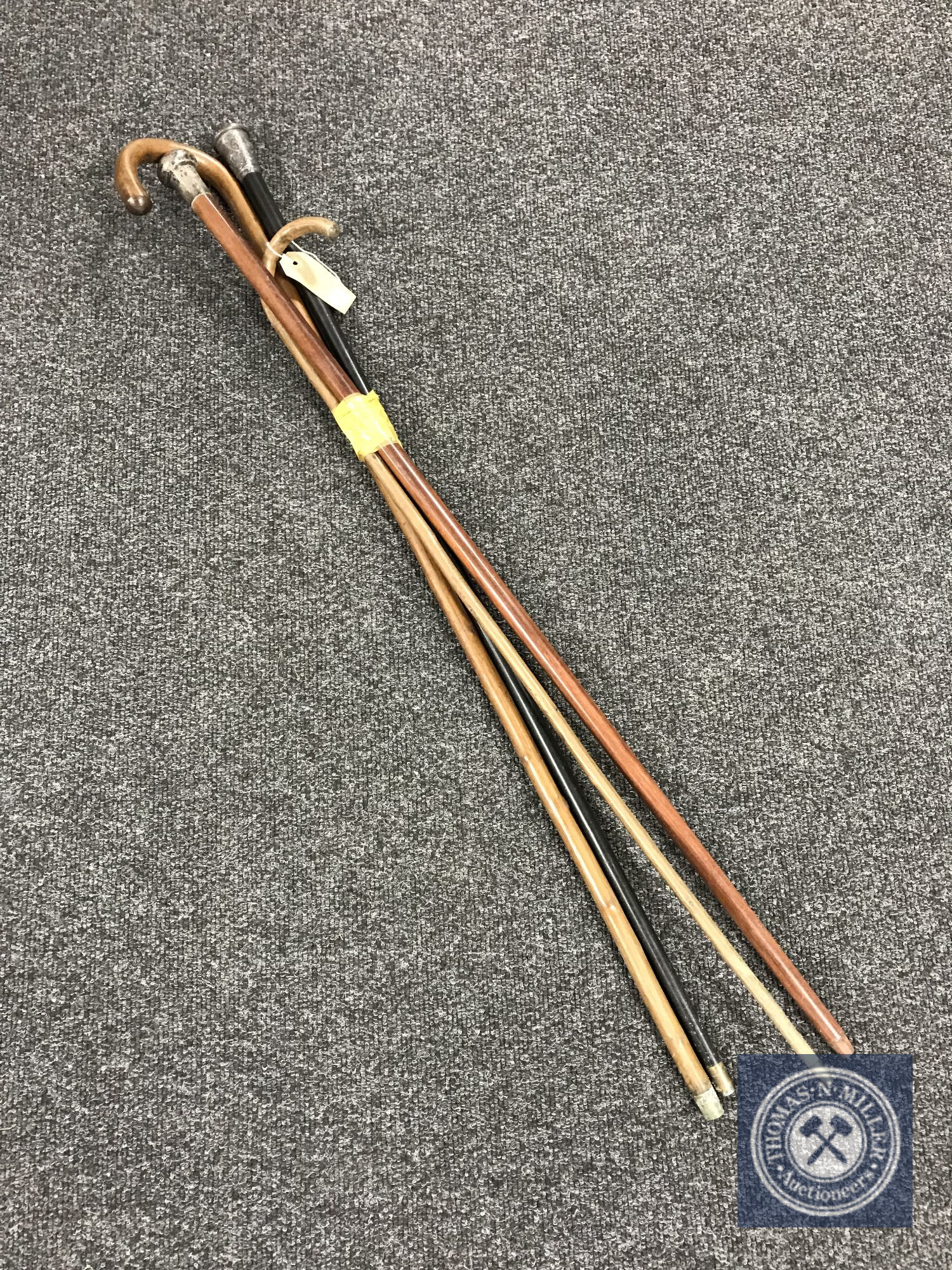 Lot 24 - Two walking sticks together with two walking canes with silver mounts