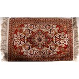 Two 20th Century Persian silk base small rugs, decorated with typical rosette motifs. (2)