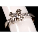 An 18ct white gold and diamond set ring, with cross-crown top over pierced shoulders.
