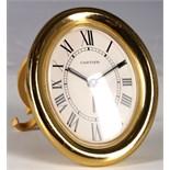 A circa 1980s gold plated Cartier oval strut clock.