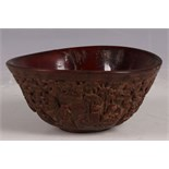 A Chinese ox horn bowl, carving to flank of the eight immortals in garden / forest scene, 12.5cm