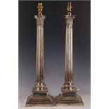 A pair of mid 20th Century, Corinthian column shaped, silver plated lamp bases, raised on stepped