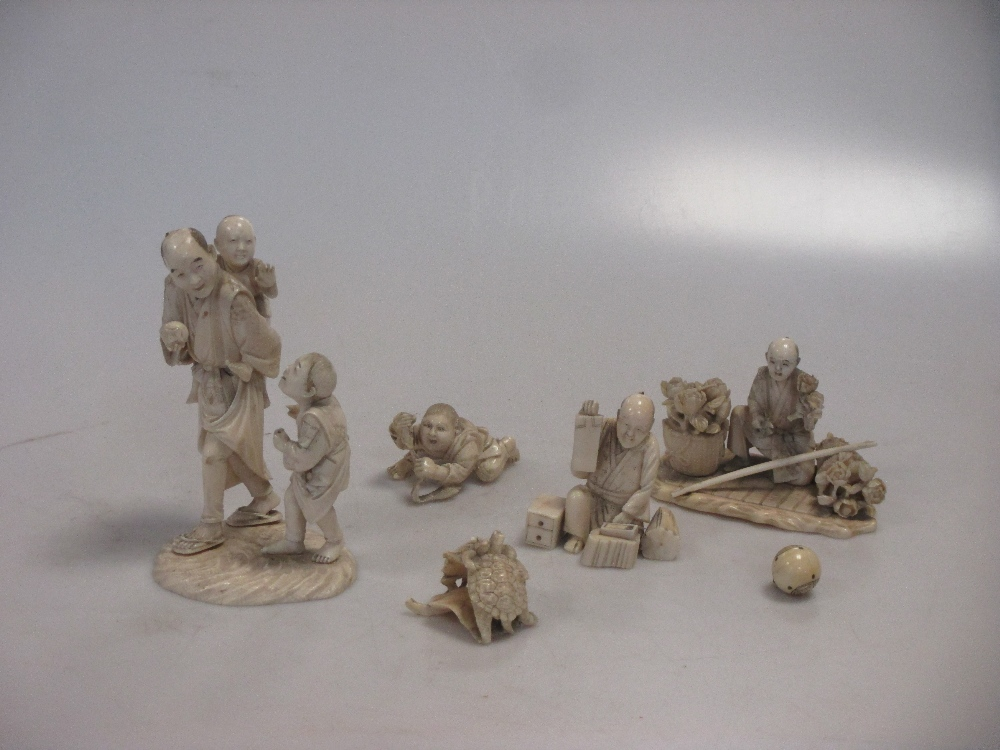 Lot 136 - Two Japanese carved Okimono figure groups depicting merchants; a figure of a father and two sons;