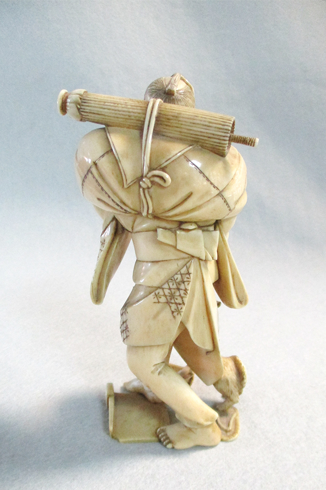 Lot 132 - An ivory okimono of a man with a fish basket, Meiji period, finely carved, the figure carrying on