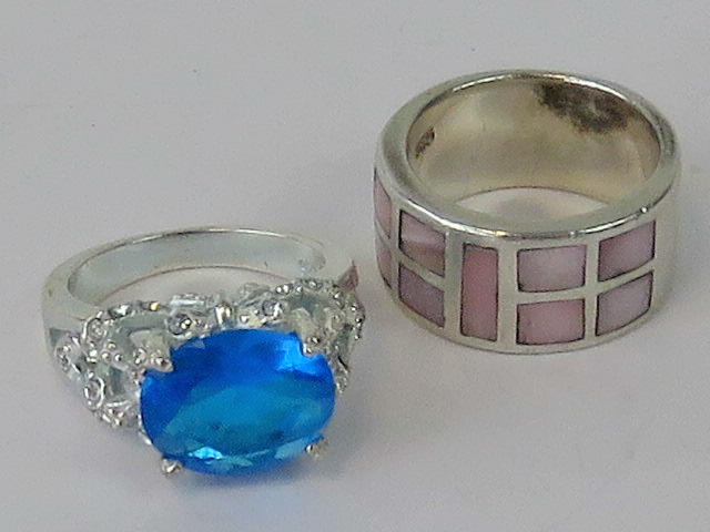 Lot 147 - Two silver rings; one set with pink moth