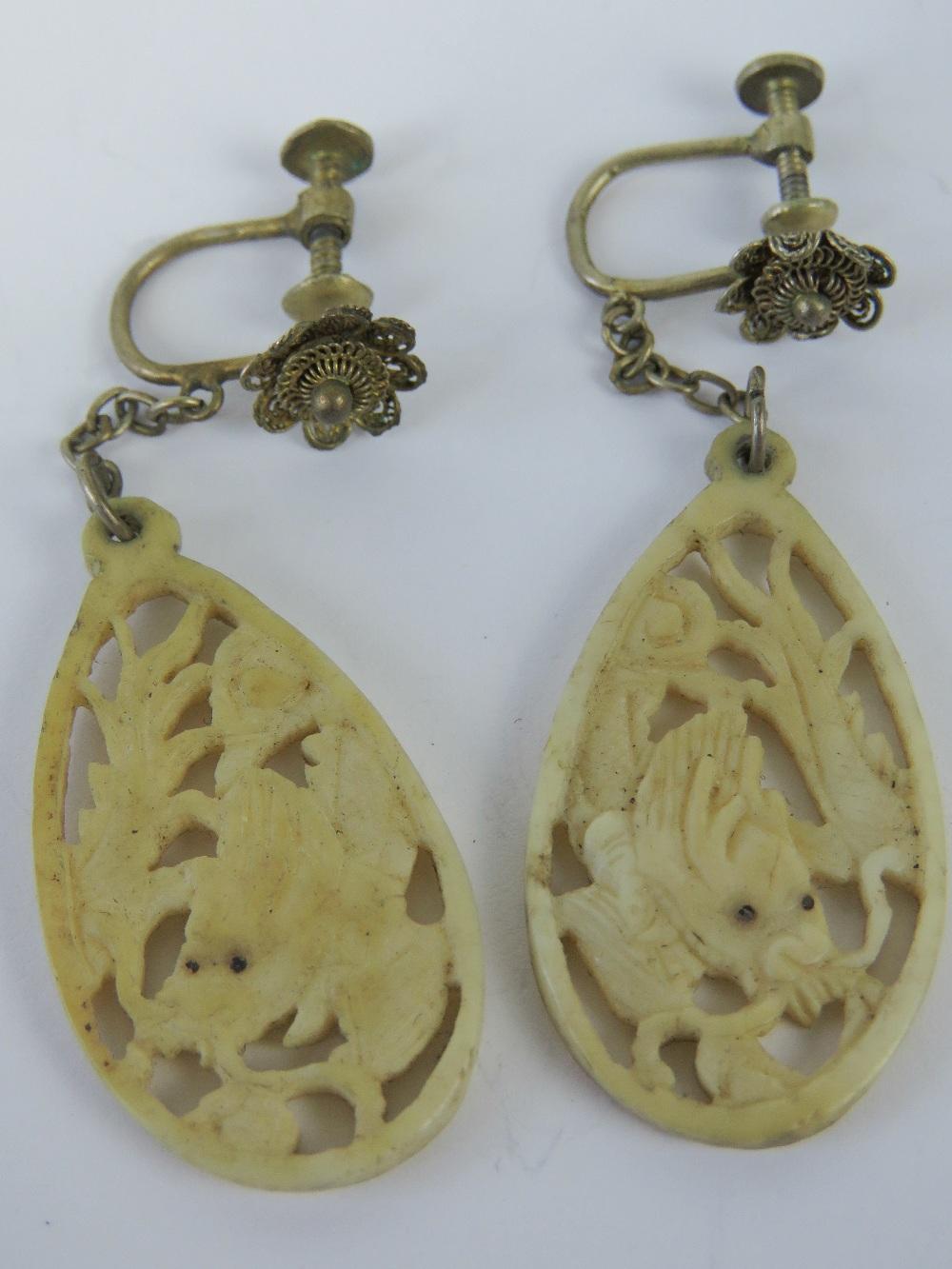 Lot 48 - A pair of carved bone earrings depicting