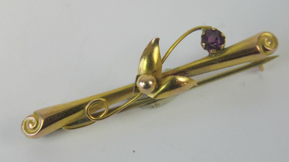 Lot 64 - A 9ct gold and amethyst bar brooch, flor