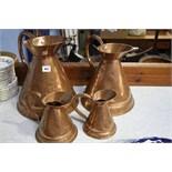 4 Graduated copper jugs