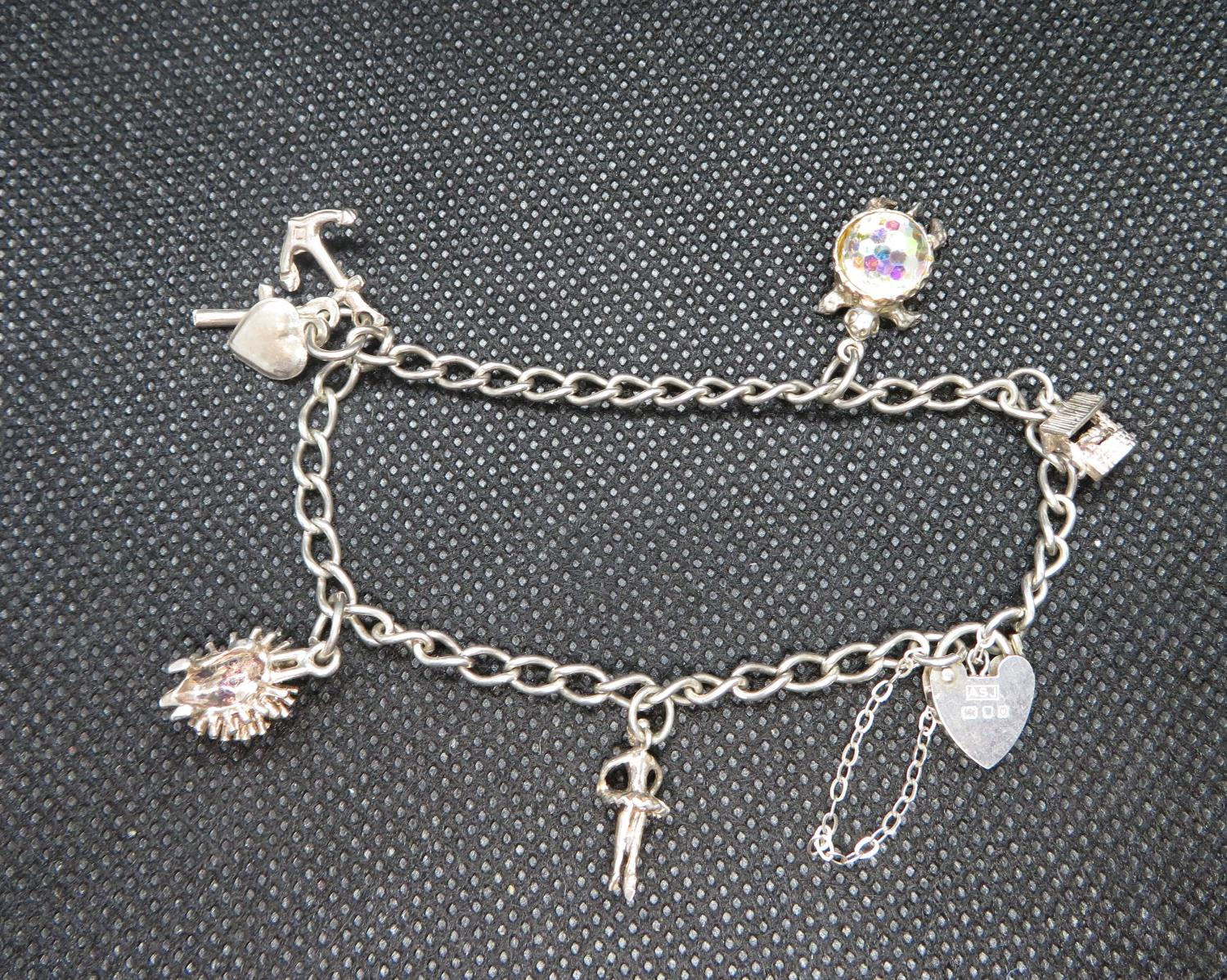 Lot 34 - Silver charm bracelet with 5 dainty charms HM London 1988 11g