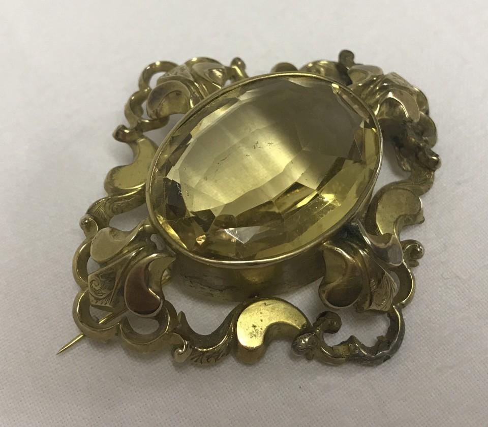 Lot 16 - A vintage large ornate 9ct gold & citrine brooch.