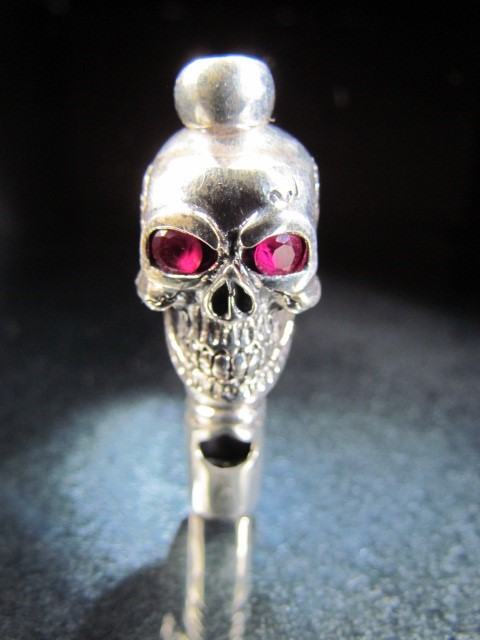 Lot 11 - Silver Skull whistle set with Ruby eyes.